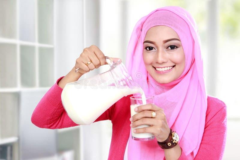 Latte di versamento della giovane donna musulmana in un vetro fotografia stock