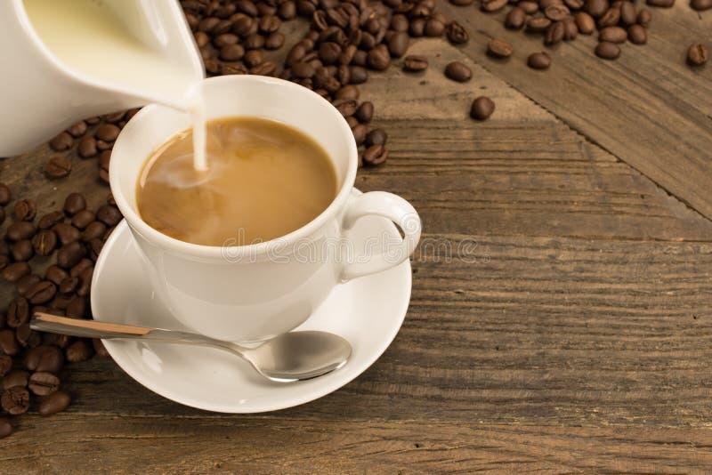 Latte di versamento in una tazza di caffè fotografie stock