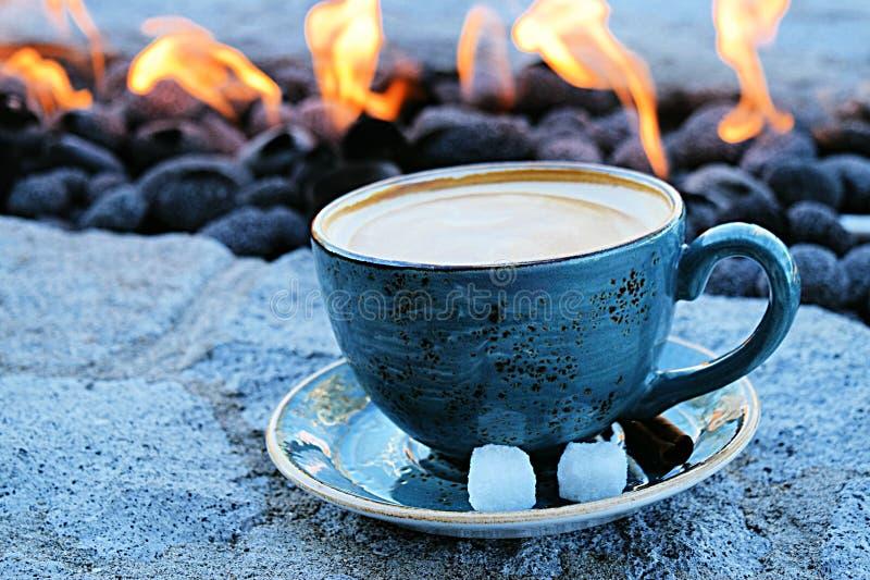 Latte do café em uma caneca cerâmica azul por um poço de pedra moderno do fogo imagem de stock