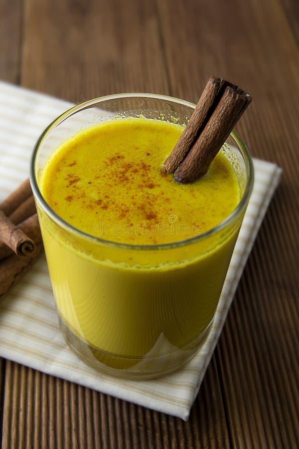 Latte dorato della curcuma Bevanda sana fatta con il miele e la cannella della curcuma Rimedio a molte malattie Priorità bassa di fotografie stock libere da diritti