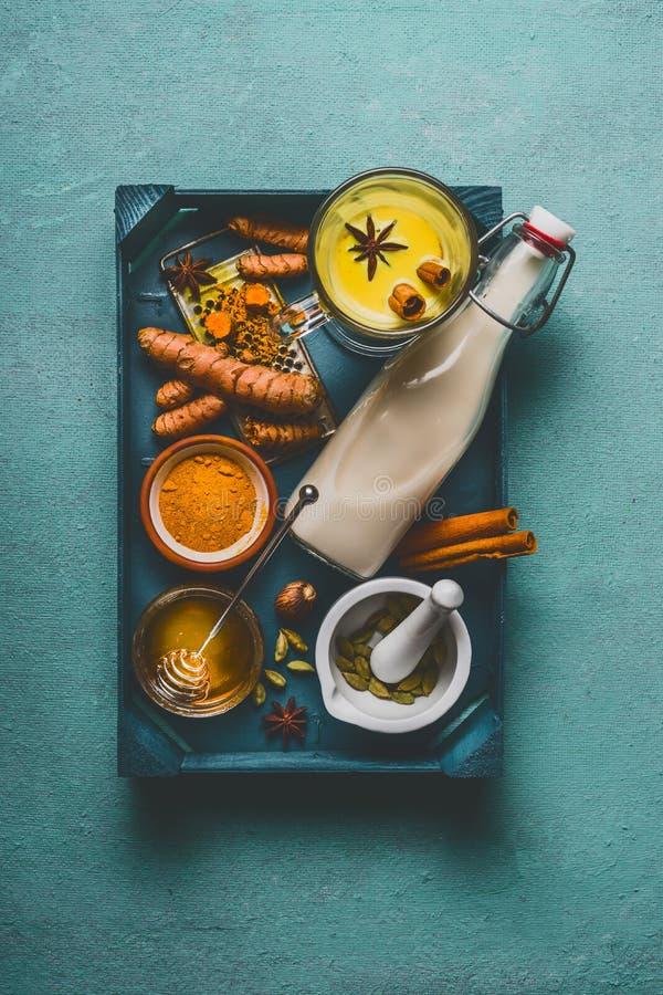 Latte dorato sano della curcuma sul vassoio con gli ingredienti: cardamomo, curcuma, cannella, miele e zenzero su fondo blu immagine stock libera da diritti