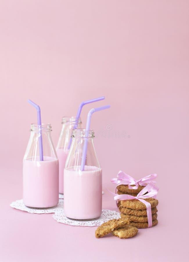 Latte e biscotti della fragola sul colore rosa immagine stock
