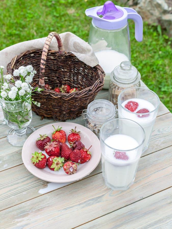 Latte e fragole mature Composizione in estate su una tavola di legno Colpo verticale immagine stock libera da diritti