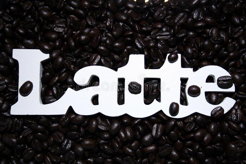 Latte em feijões de café foto de stock