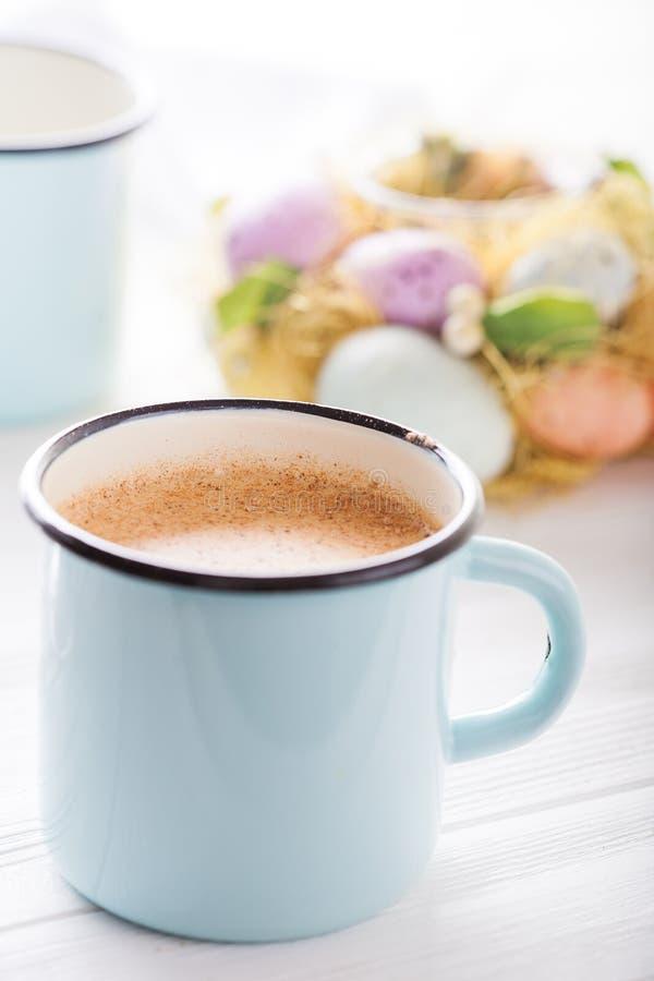Latte em um copo azul do esmalte com ovos e as flores coloridos no fundo Fim acima fotografia de stock