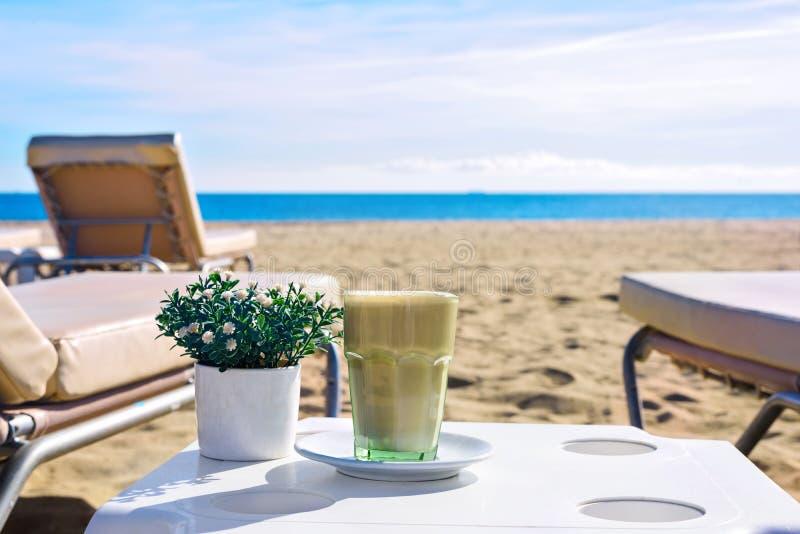 Latte en la playa Café helado Frappuccino o frappe en un vidrio alto Fondo Barcelona España de la opinión del mar imagen de archivo