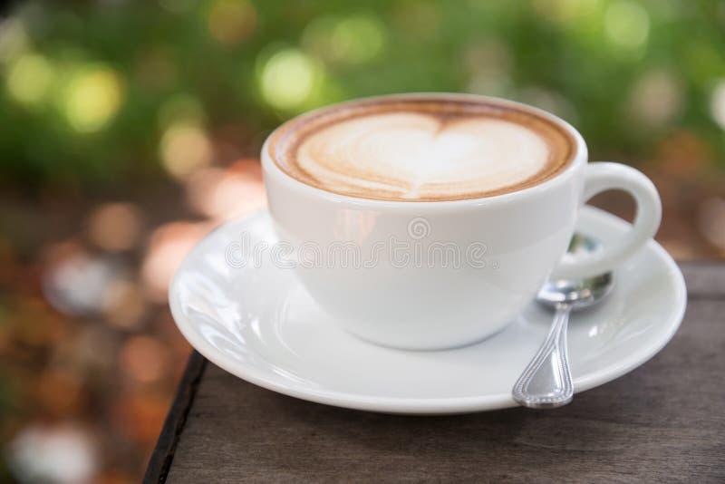 Latte en la taza de cerámica blanca con el platillo en fotografía macra imagen de archivo