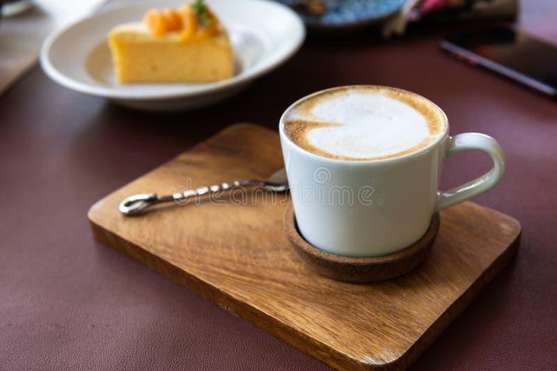 Latte filiżanka z łyżką na drewnianym talerzu obrazy royalty free