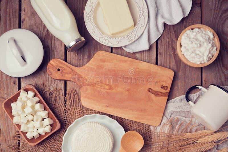 Latte, formaggio e burro con il tagliere su fondo di legno Vista da sopra fotografia stock