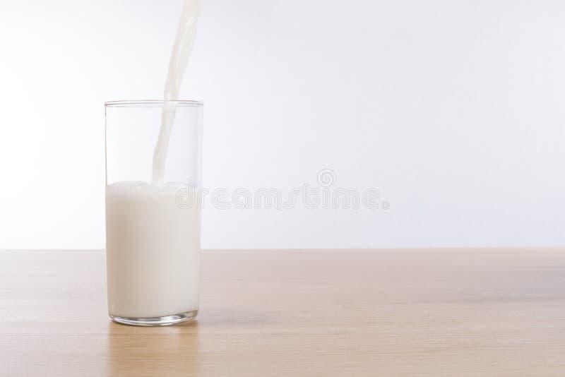 Latte fresco che versa in un vetro su una cima del banco fotografia stock libera da diritti