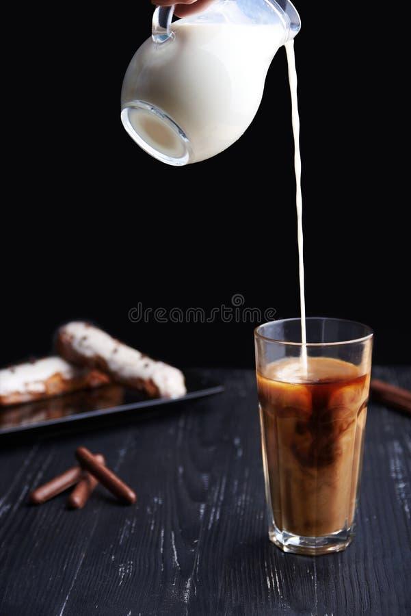 Latte fresco di versamento in un vetro Foto scura immagini stock