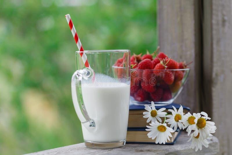 Latte fresco sulla tavola di legno con le bacche immagini stock libere da diritti