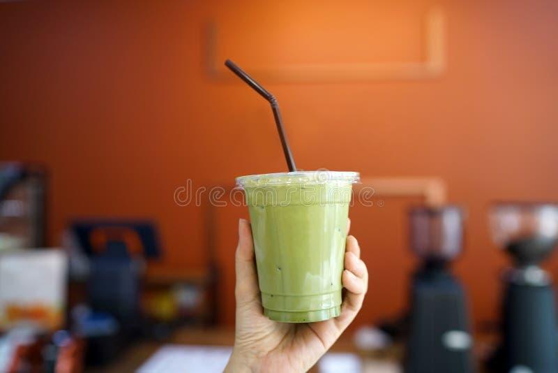 Latte ghiacciato di matcha - tenere un vetro di plastica di tè verde con latte su fondo vago fotografia stock