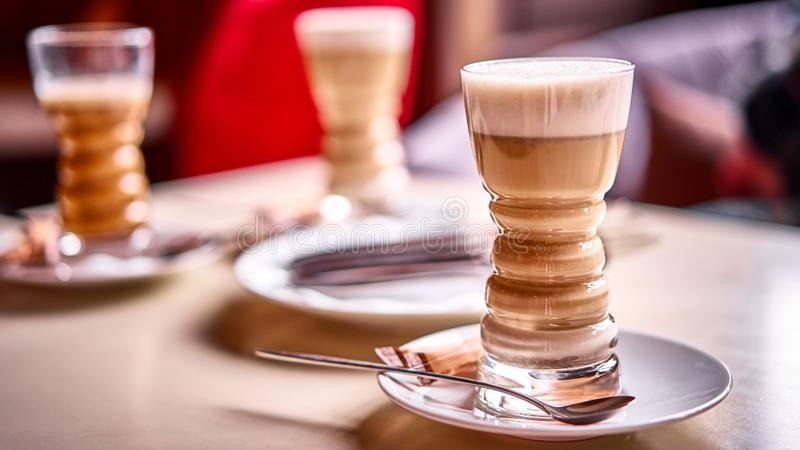 Latte glass with layered latte, cappuccino or mocha with foam on table in cafe with milk saucer and spoon. Three cups of. Coffee. Food and drink toning image royalty free stock images