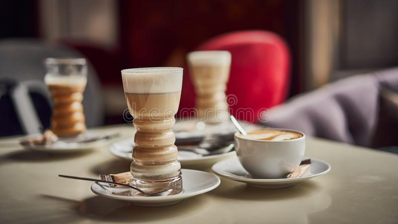 Latte glass with layered latte, cappuccino or mocha with foam on table in cafe with milk saucer and spoon. Three cups of. Coffee. Food and drink toning image royalty free stock photography