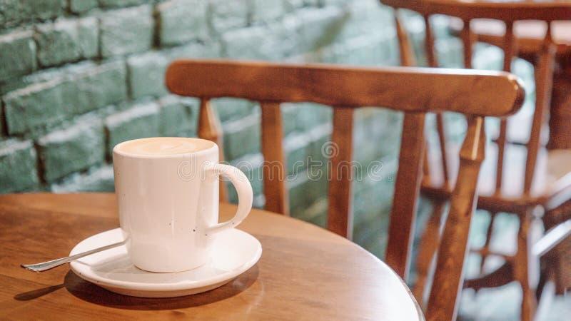 Latte grande branco da xícara de café na tabela no fundo da parede de tijolo formato panor?mico do 16:9 imagem de stock