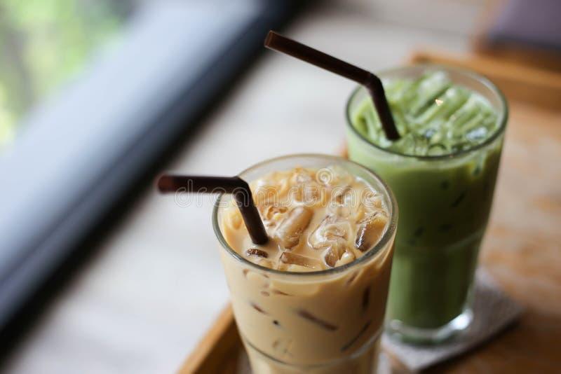 Latte helado del té verde y del café en la tabla de madera foto de archivo
