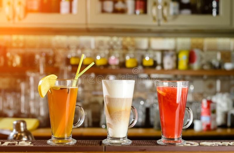 Latte and hot alcoholic cocktails at the bar counter in rays of. The sun royalty free stock image