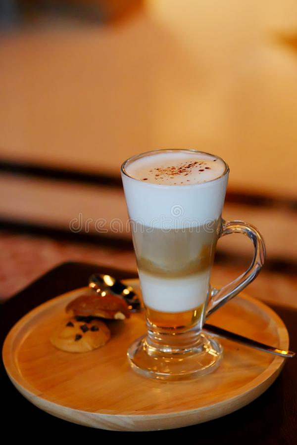 Latte macchiato coffee Served with cookie in brown earth tone color background royalty free stock photo