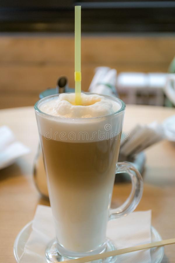 Latte macchiato in tall glass on the table. stock photography