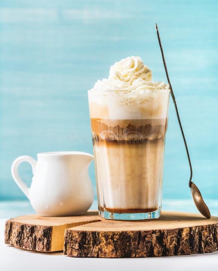 Latte macchiato z batożącą śmietanką, słuzyć srebną łyżką i białym miotaczem na drewnianej round desce nad błękit malującą ścianą fotografia royalty free