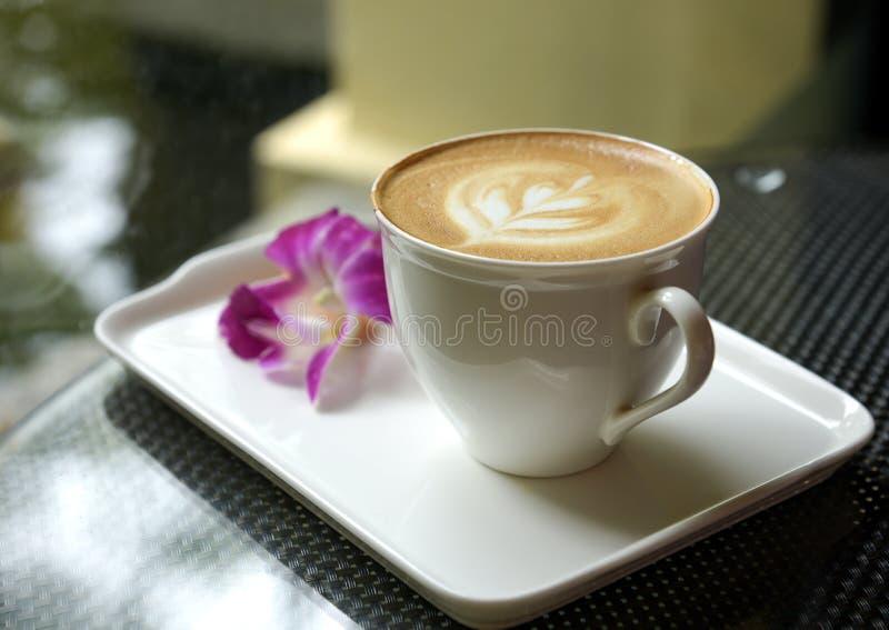 Latte na caneca branca na bandeja cerâmica com plumeri borrado fotografia de stock