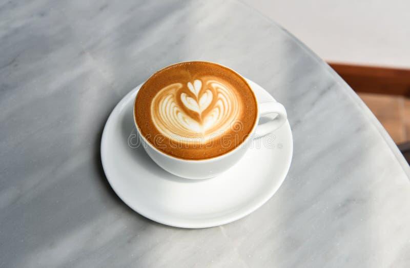 Latte ou cappuccino avec la mousse ?cumeuse, vue sup?rieure de tasse de caf? sur la table en caf? photographie stock libre de droits