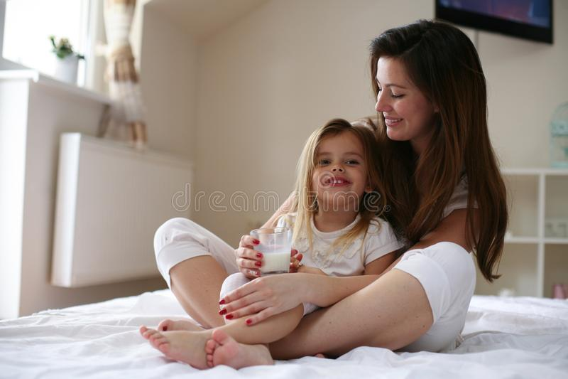 Latte prima del letto Routine di sera della figlia e della madre immagini stock
