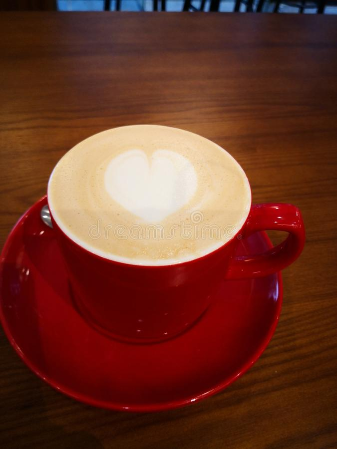 Latte in red cup with heart shape decorated royalty free stock photography