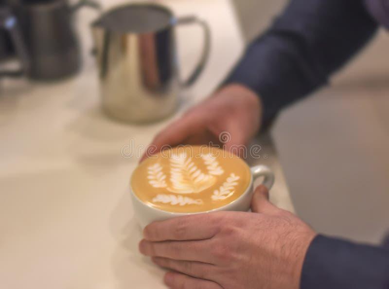 Latte saboroso fresco do café com arte do latte nas mãos do barist no bar imagem de stock royalty free