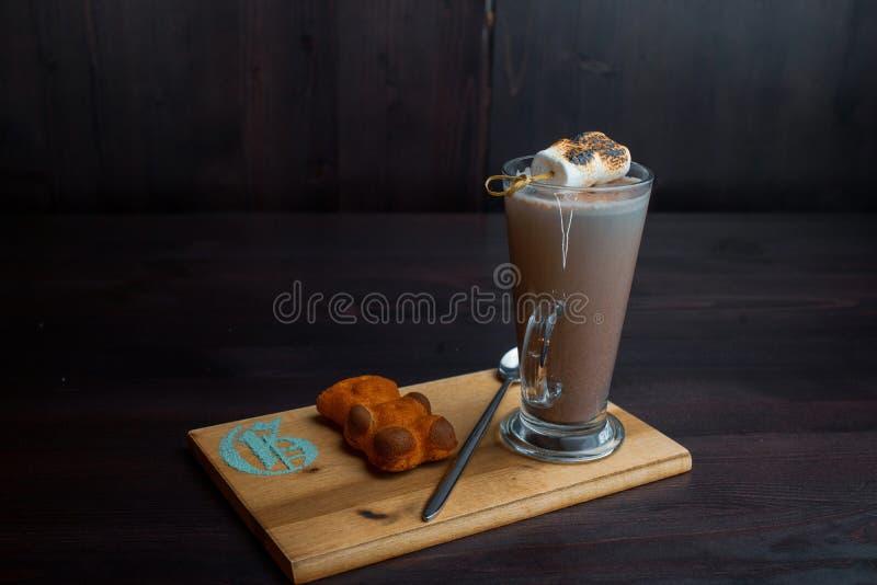 Latte saporito dolce caldo in un vetro trasparente con il biscotto decorato con la caramella gommosa e molle aerea su un bordo di immagine stock