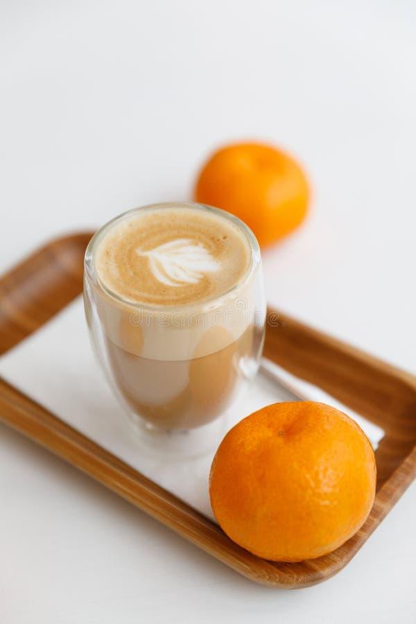 Latte su un vassoio di legno e sui mandarini Pausa caffè accogliente a casa immagine stock