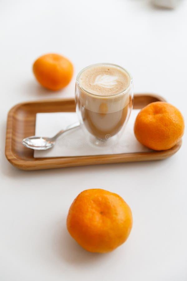 Latte su un vassoio di legno, sulle candele e sui mandarini Pausa caffè accogliente a casa immagine stock
