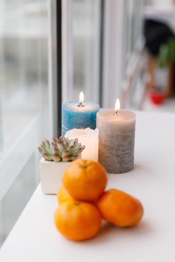 Latte su un vassoio di legno, sulle candele e sui mandarini Pausa caffè accogliente a casa immagini stock libere da diritti