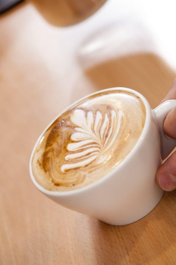 Latte sztuka w kawy espresso filiżance na Drewnianej powierzchni zdjęcia stock