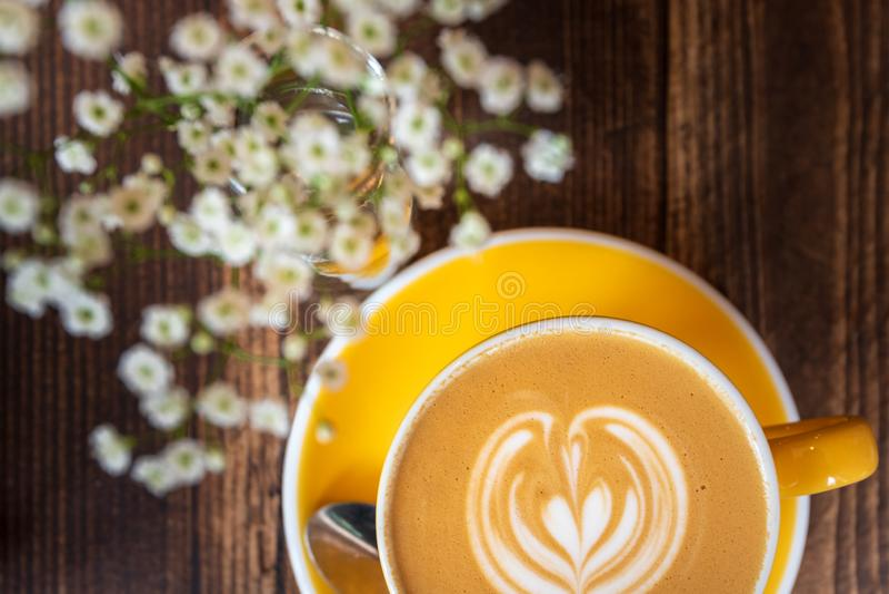 Lattecoffe i ljust gult kopp och tefat bredvid några blommor på en trätabell royaltyfri bild