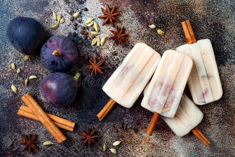 Latteeis am stiel Masala Chai mit Feigen auf Zimtstangen Gewürzte Eislutscher für Fall, Wintersaison Weihnachtsfeiertagsnachtisch stockfotografie