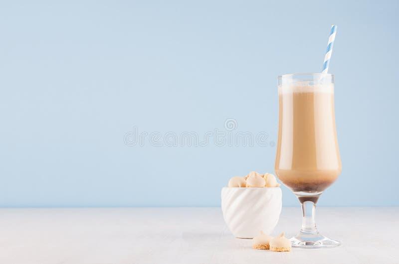 Lattekaffe i elegant genomskinligt exponeringsglas med skum, sugrör och kex i den vita bunken i modern ljus pastellfärgad blå kök royaltyfri bild