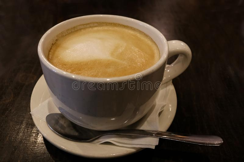 Lattekaffe med skum i en vit kopp med skeden på en mörk tabell arkivbild