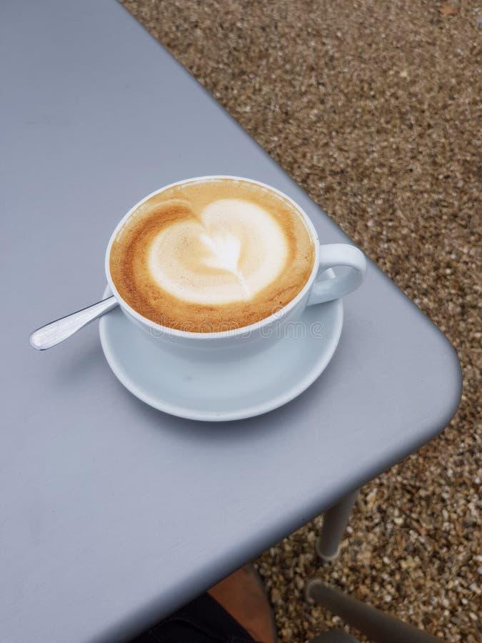Lattekaffe mycket till brättet i en porslinkopp fotografering för bildbyråer