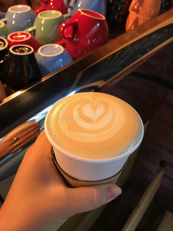 Lattekoffie, cappuccino in een beschikbare document kop met het beeld van een bloem - een hart tegen de achtergrond van heldere m royalty-vrije stock afbeelding