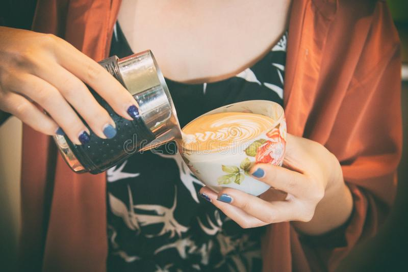 Lattekonst vid den kvinnliga baristafokusen i mjölkar och kaffe i tappningfärgeffekt hand av baristaen som gör latte- eller cappu arkivfoto