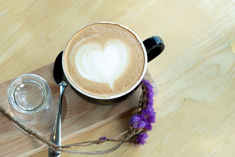 Lattekonstkaffe i morgontiden med solljus på trätabellbakgrund på coffee shop royaltyfri fotografi