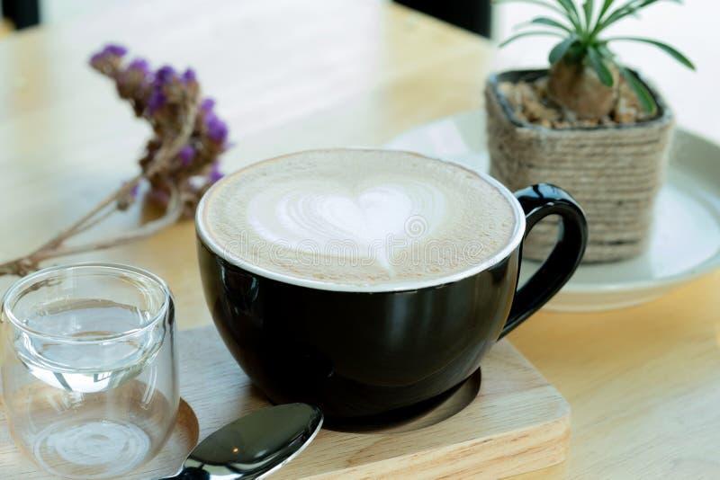 Lattekonstkaffe i morgontiden med solljus på trätabellbakgrund på coffee shop royaltyfria bilder