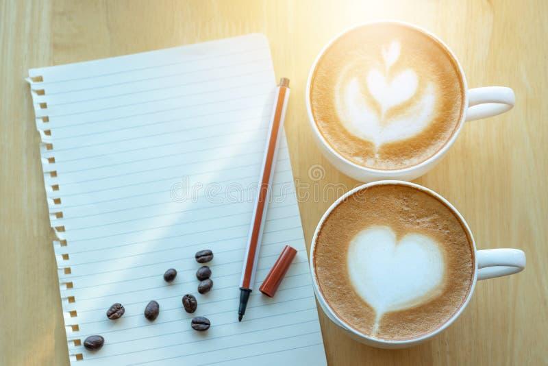 Lattekonstkaffe och grillade kaffebönor med papernote på morgonen arkivbild