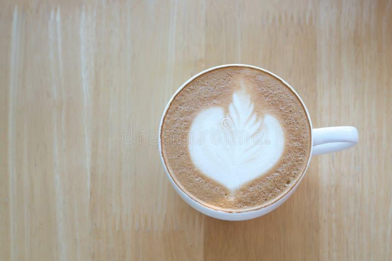 Lattekonstkaffe på trätabellbakgrund arkivfoton