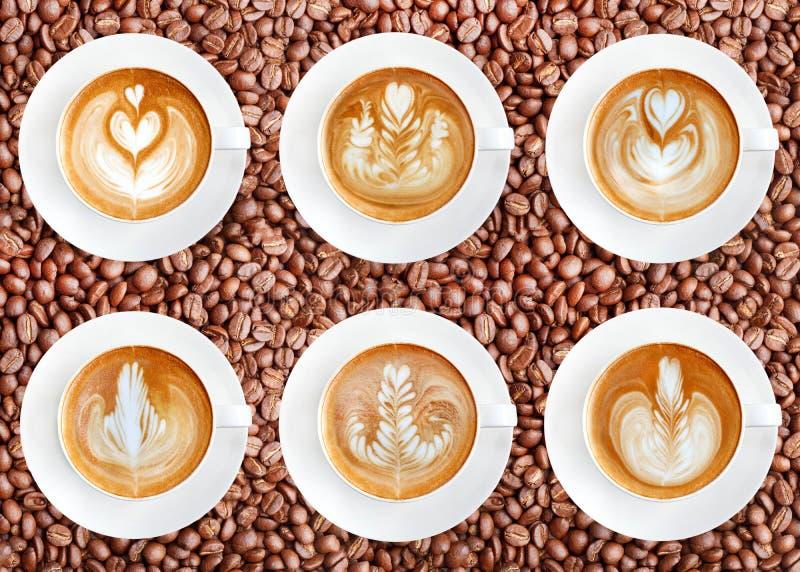 Lattekunstkaffee auf Röstkaffeebohnenhintergrund lizenzfreie stockbilder