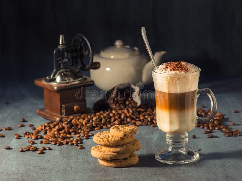Lattemacchiato in een lang glas met chocolade bestrooit Op de achtergrond zijn er gemorste koffiebonen en een koffiemolen royalty-vrije stock afbeeldingen
