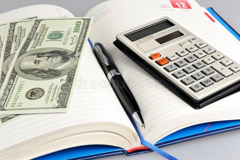 Latteria con il primo piano nero della penna, del calcolatore e dei soldi fotografia stock