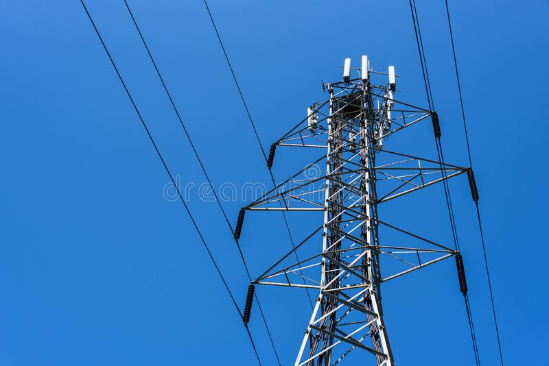 Lattice self-supporting steel utility tower with power lines and panel antennas for a wireless communications network, bird nest o. N top, bright blue clear sky stock image